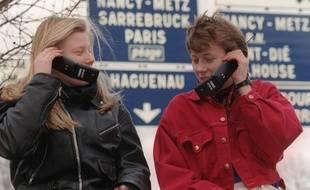 Deux jeunes femmes passent des communications à l'aide du nouveau téléphone