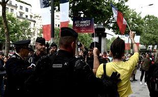 Des gendarmes entourent une manifestante sur les Champs-Elysées, le 14 juillet.
