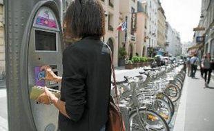 Les usagers déposent leur carte d'abonné contre la borne et retirent un Vélib'.