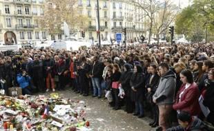 Des personnes rassemblées devant le Bataclan observent une minute de silence, le 16 novembre 2015 à Paris, après les attentats meurtriers