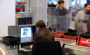 Un officier des douanes scanne les bagages à l'aéroport de Roissy Charles de Gaulle (Paris).