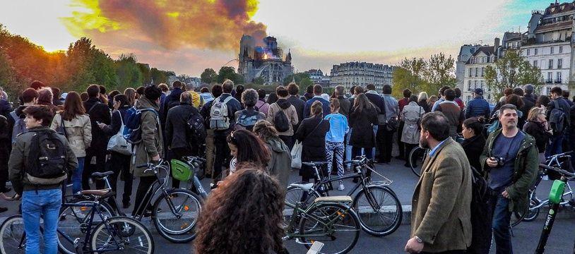 Des passants observent l'incendie de Notre-Dame de Paris le 15 avril 2019