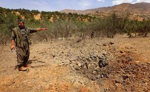 Un membre du Parti des travailleurs du Kurdistan (PKK) inspecte un cratère causé par un raid de l'armée turque, sur le mont Qandil au nord de l'Irak, le 29 juillet 2015