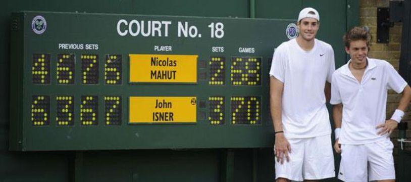 Nicolas Mahut (à droite), pose à côté du tableau d'affichage avec John Isner, le 24 juin 2010, à Wimbledon.