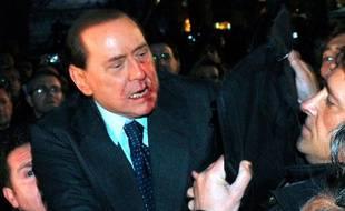 Le Premier ministre italien Silvio Berlusconi est secouru par la police après avoir été attaqué par un homme lors d'un meeting électoral, Milan, le 13 décembre 2009.