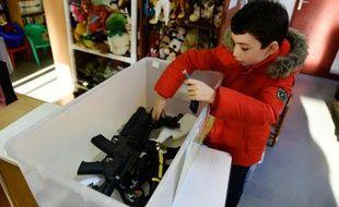 Edouard, 9 ans, dépose des jouets factices dans une caisse en plastique, à Ris-Orangie (Essonne), le 9 décembre 2015