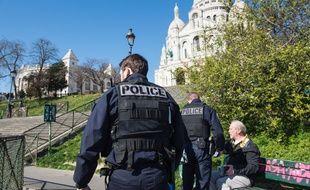 Des policiers contrôlent les attestations de déplacement de Parisiens dans le quartier de Montmartre, ici le 23 mars.
