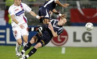 Olympique Lyon's Karim Benzema (L) challenges Enrique (C) and Mathieu Chalme (R) of Bordeaux during their French Ligue 1 soccer match at the Gerland stadium in Lyon March 9, 2008. REUTERS/Robert Pratta