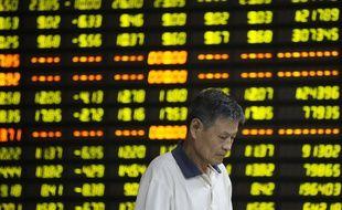 Un homme passe devant un tableau des cours financiers à Huaibei, dans la province chinoise d'Anhui, le 27 juillet 2015.