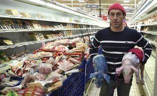 Un éleveur avec deux porcelets lors d'une opération coup-de-poing au supermarché Cora à Pacé, près de Rennes.
