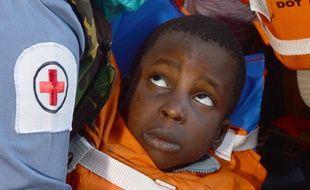 Une assistante médicale de la Royal Navy prend en charge un enfant sauvé au large des côtes libyennes le 13 mai 2015.