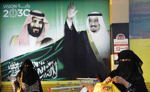 Deux femmes passent devant des portraits du roi Salman et du prince Mohammed ben Salman, le 5 février, à Djeddah, en Arabie saoudite.