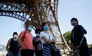 Des touristes au pied de la Tour Eiffel après plusieurs semaines de fermeture à cause de la pandémie de coronavirus.