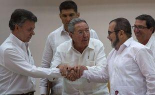 Le président colombien et le commandant des Farc se serrent la main avec la bénédiction de Raul Castro le 23 septembre 2015 à La Havane.