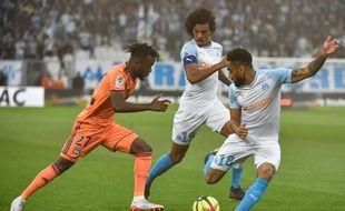 Le joueur de l'OL Maxwell Gnaly Cornet  face aux Marseillais Luiz Gustavo et Jordan Amavi lors du match de Ligue 1 OM-Ol le 12 mai 2019.
