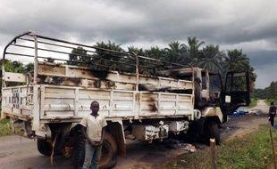 Un garçon congolais se tient devant le camion de la Mission de l'ONU détruit dans une embuscade la veille qui a provoqué la mort de deux soldats tanzaniens, dans la ville de Beni, le 5 mai 2015