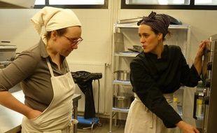 Marion et Mélanie testent four et autre matériel dans la cuisine partagée des Camionneuses.