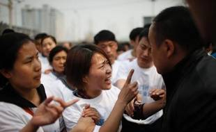 Des proches des victimes du vol MH370 manifestent leur colère, à Pékin le 25 mars 2014