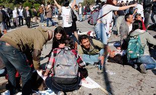 Des manifestants tentent d'aider des victimes des explosions qui ont touché un défilé pour la paix à Ankara en Turquie, le 9 octobre 2015