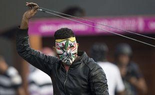 Un palestinien masque se prépare à lance rune pierre avec une fronde à Ramallah, le 9 octobre 2015
