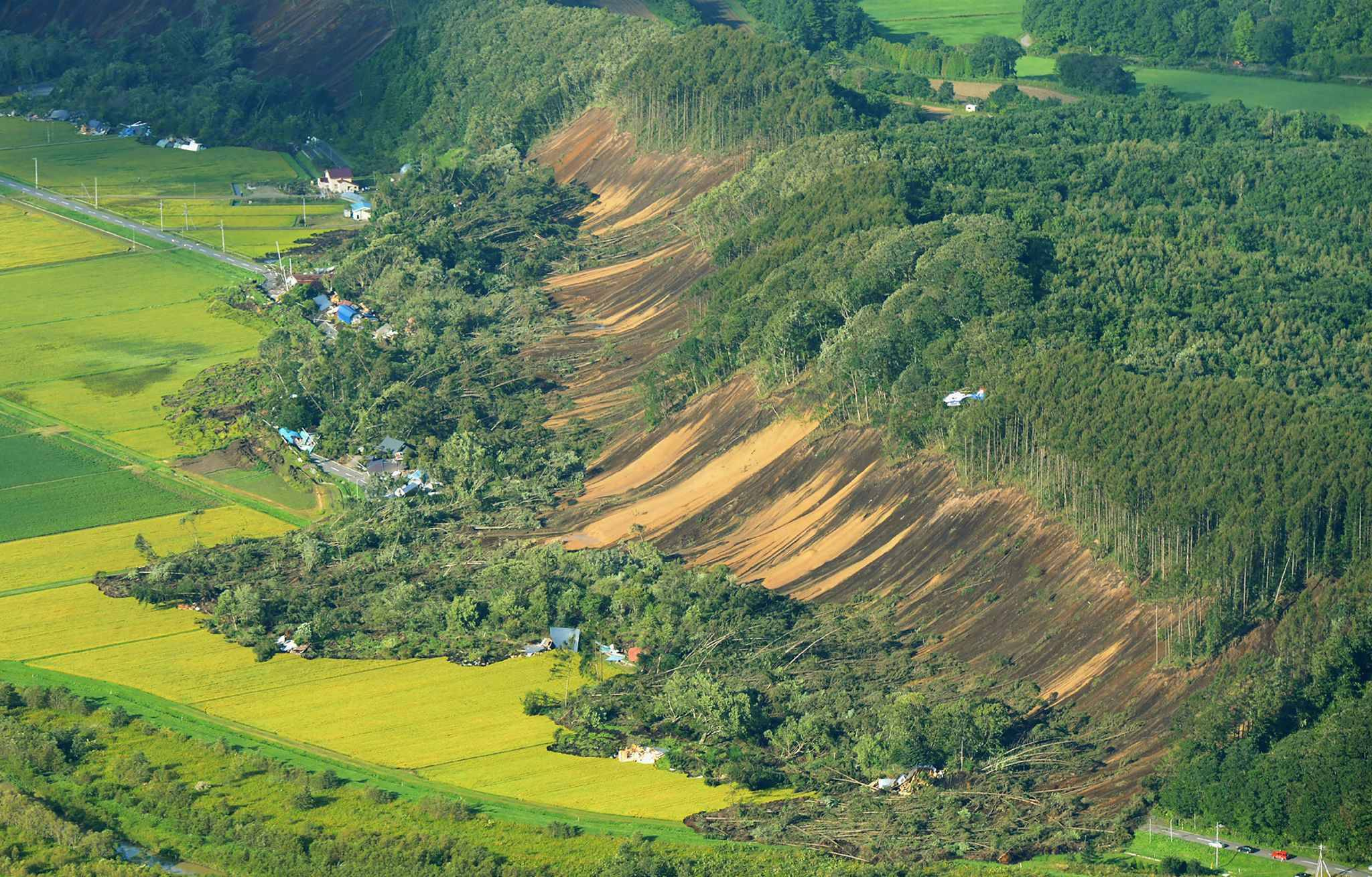 This picture shows an aerial view of houses damaged by a landslide in Atsuma town, Hokkaido prefecture on September 6, 2018, after an earthquake hit the northern Japanese island of Hokkaido. A powerful 6.6 magnitude quake hit the northern Japanese island of Hokkaido on September 6, triggering landslides, bringing down several houses, and killing at least one person with several dozen missing.