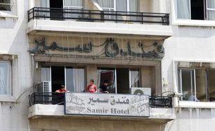 """Ce sont les nouveaux """"touristes"""" de Damas: dans des hôtels décrépits, des dizaines de familles de déplacés vivent, certaines depuis plus d'un an, entassées dans des chambres de 15m2 où elles cuisinent dans la salle de bain et s'empruntent la machine à laver."""