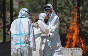 Un parent d'une personne décédée du COVID-19 est consolé par une autre lors de l'incinération du corps, à Jammu, en Inde, le 25avril 2021.