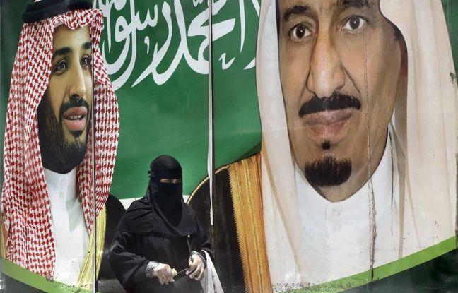 648x415 une femme saoudienne devant une affiche a la gloire du roi salmane et du prince heritier mohammed