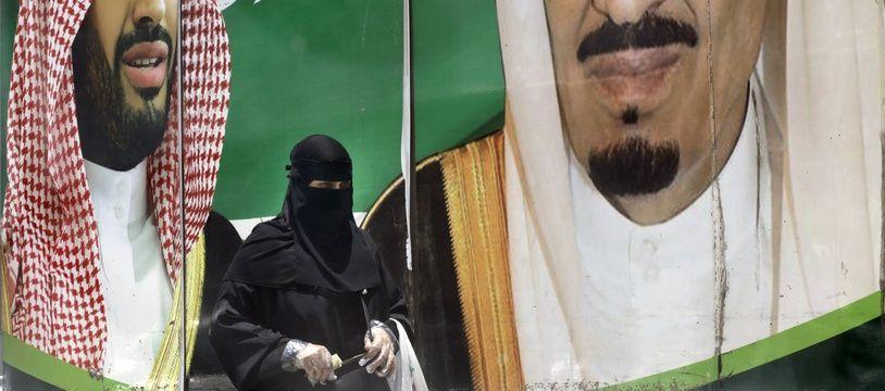 Une femme saoudienne devant une affiche à la gloire du roi Salmane et du prince héritier Mohammed ben Salmane, à Djeddah le 15 juin 2020.