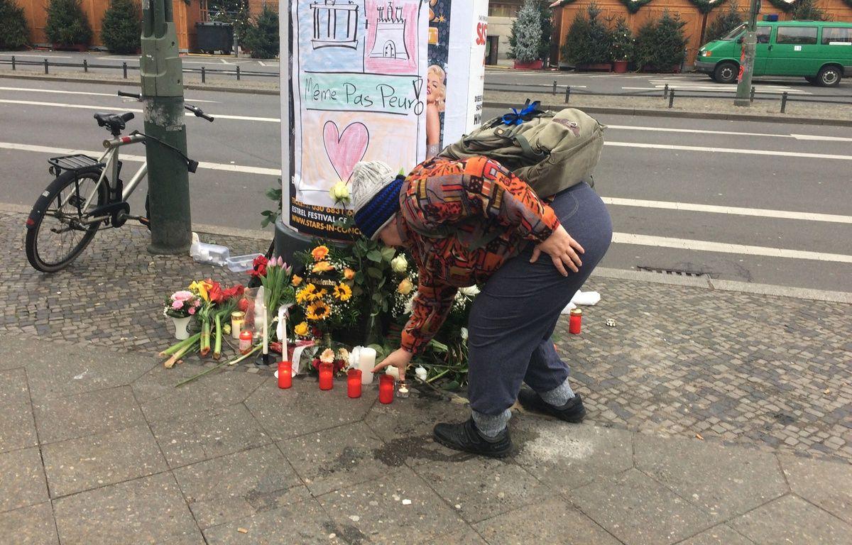 Une femmes déposes des fleurs en hommages aux victimes contre l'attentat de Berlin le 20 décembre 2016. – Jacques PEZET / 20 Minutes