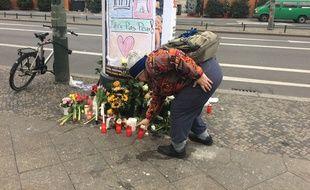 Une femmes déposes des fleurs en hommages aux victimes contre l'attentat de Berlin le 20 décembre 2016.