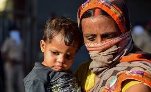 Une femme et son enfant attendent un bus du gouvernement qui les ramènera dans leur région, à Bombay le 19 mai 2020.