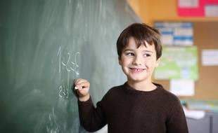 Un petit garcon au tableau, dans une salle de classe, France.