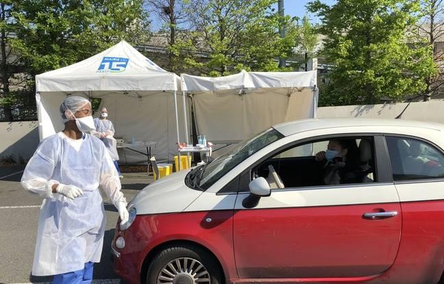 Paris, le 20 avril 2020. Un biologiste s'apprête à effectuer un prélèvement naso-pharyngé sur une jeune femme afin de vérifier s'il est porteuse du Covid-19 ou pas.