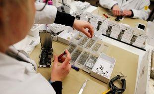 Une femme employée de l'usine Remade de Poilley travaille sur un téléphone reconditionné.