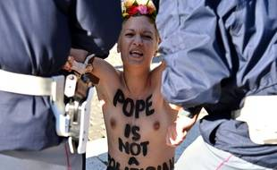 A topless Femen activist is arrested as she protests with other Femen in St Peter's square on November 14, 2013 at the Vatican. They protest against the Pope's planned visit at EU parliament as an attack on secularism. AFP PHOTO / ALBERTO PIZZOLI