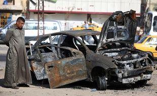 Inspection d'une voiture piégée à Bagdad, en Irak, après une attaque le 3 juillet 2013.