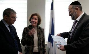 Beate Klarsfeld (C) reçoit des mains du ministre de l'Intérieur israélien Arye Deri (D) et du directeur du mémorial de Yad Vashem, Avraham Shalev, sa carte d'identité et son passeport israéliens, lors d'une cérémonie au minstère de l'Intérieur à Jérusalem, le 15 février 2016