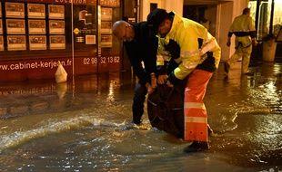 Des agents municipaux soulèvent une plaque d'égout dans une rue inondée à Morlaix, le 4 juin 2018.