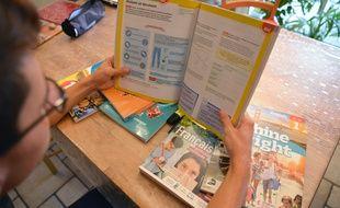 Un élève de première découvre ses manuels.