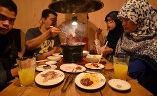 Des touristes thaïlandais musulmans dégustent des mets certifiés halal dans un restaurant de Tokyo, le 24 juin 2014