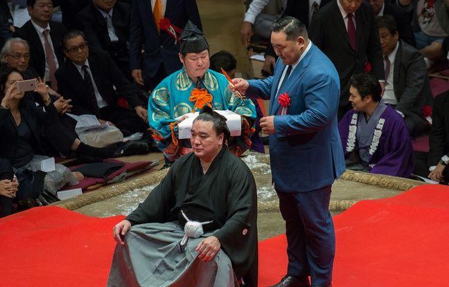 L'ex champion de sumo mongol Asashoryu coupe une mèche du yokozuna Harumafuji à Tokyo, le 30 septembre 2018.