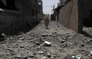 Un homme marche au milieu des décombres des bâtiments qui ont été touchés lors de frappes aériennes israéliennes, dans une rue de la ville de Gaza, le 16 mai 2021.