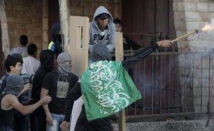 Des palestiniens utilisent des portes comme bouclier lors d'affrontements avec les forces de sécurité israéliennes dans le camps de réfugiés de Chouafat, le 6 novembre 2014