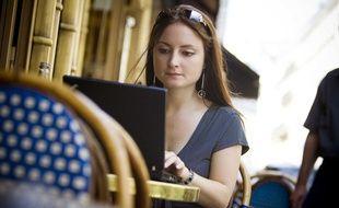 Une jeune femme qui surfe sur le web à Paris.