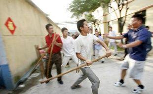 Les proches des mineurs coincés par une inondation se battent avec les officiels du gouvernement à Xintai, devant le bâtiment de la Huayuan Mining Corp