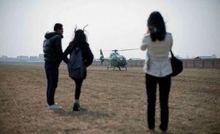 """Sur des terrains agricoles en partie transformés en piste d'atterrissage sont alignés des hélicoptères et des petits avions rutilants, qui valent des millions de dollars: Pékin compte désormais son premier """"supermarché"""" destiné aux super riches qui veulent voler."""