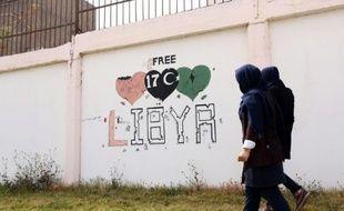 """Des étudiants passent à côté d'un graffiti """"Libye libre"""", à Tripoli, le 31 mars 2016"""