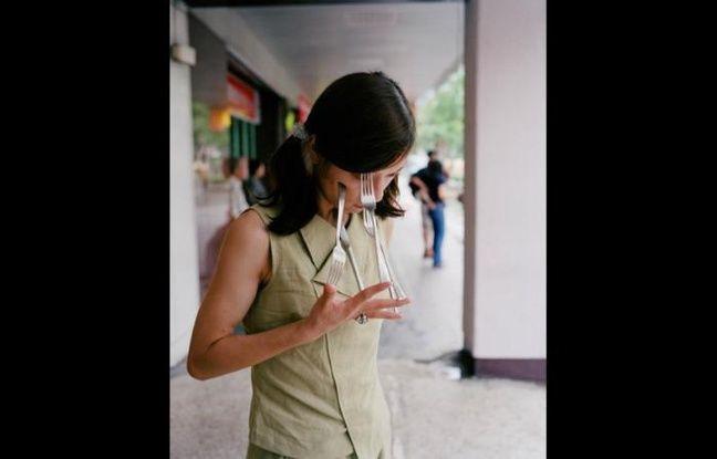 Photographie surréaliste: une jeune femme mettant trois fourchettes contre son visage