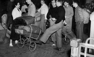 Des gens patientent dans une gare à Paris s'apprêtant à partir en vacances, pendant l'été 1936, grâce aux deux semaines de congés payés obtenus par les salariés.